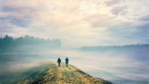 Two men, with their backs to us, walking into the fog on a causeway