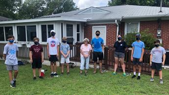 Youth volunteers in backyard with member