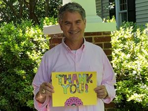"""Paul with a """"thank you"""" sign"""