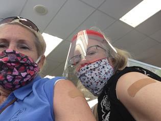 Diane and Hope wearing masks and showing flu shot bandaids