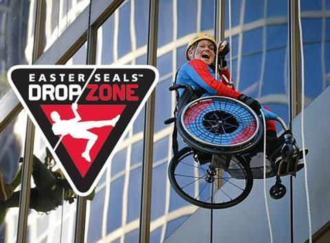 A young person in a wheelchair rappeling down a building for Drop Zone