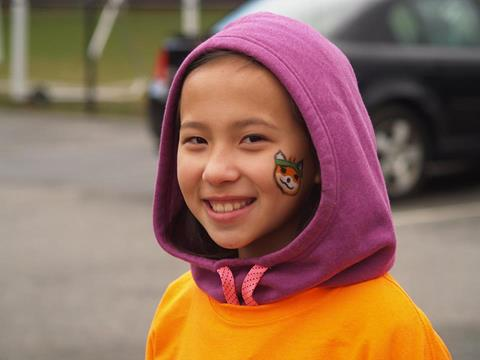 a girl with fox face paint on her cheek and an orange and purple sweatshirt