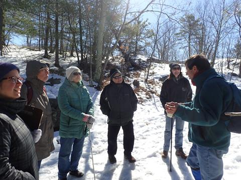Hike leader Boot Boutwell is speaking to the hikers on a snowy hill. Photo credit: Sheri Qualters