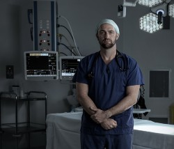 Doctor in Voice Box Campaign in scrubs in front of surgical table