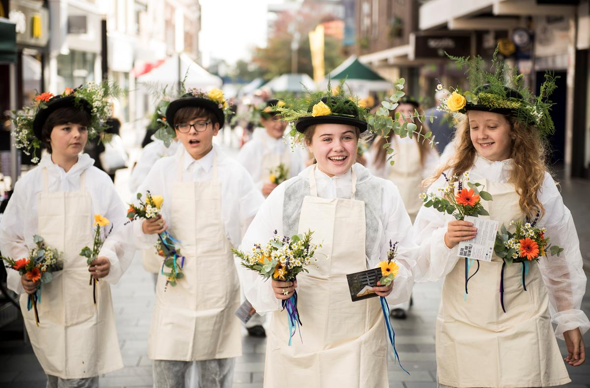 Secondary school ages young people taking part in performance art gifting posies to shoppers on the high street