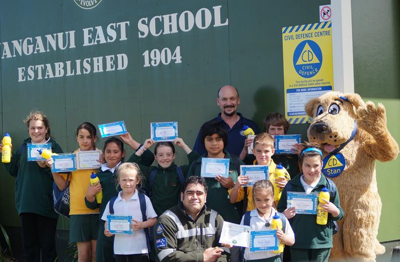 Wanganui CDEM staff with schoolchildren holding certificates.