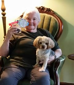 Member, Sidney, holding a birthday cupcake and her dog!