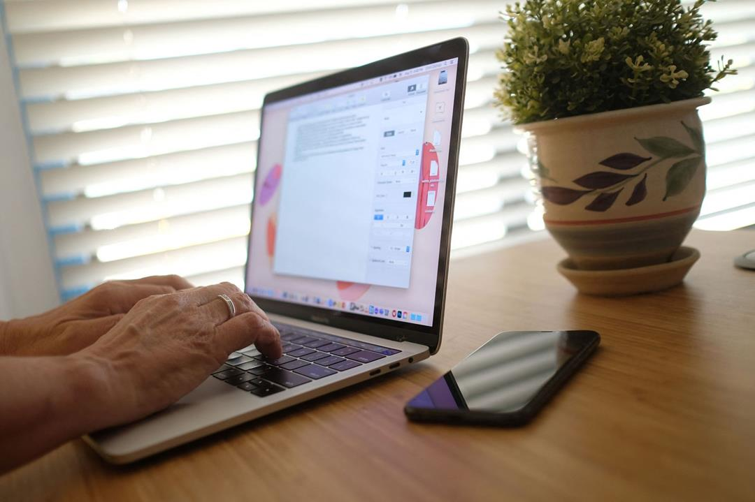 Image of a person using and typing on a laptop in a home setting.