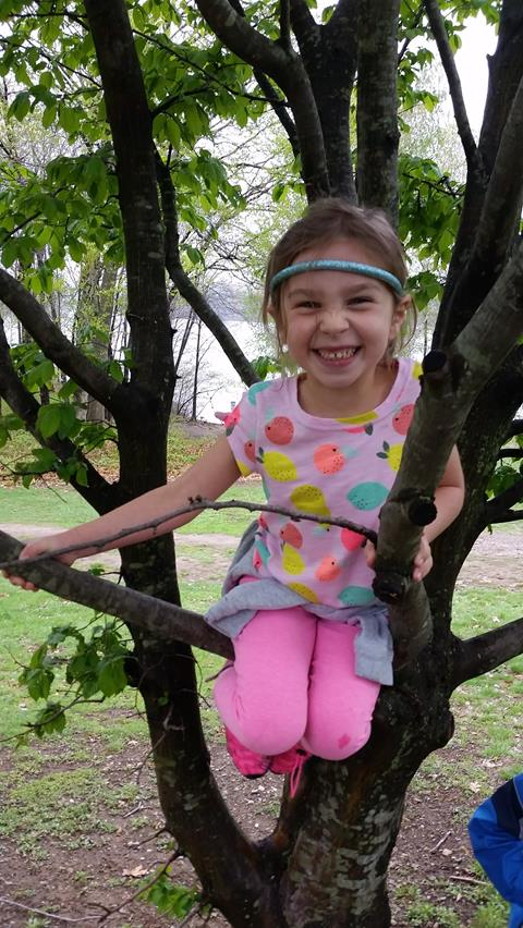 A little girl with light skin and dark hear wearing pink clothes with a fruit design sitting on the branch of a small tree with a big smile on her face