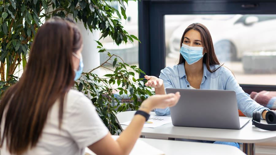 image of two women wearing masks in a work environment