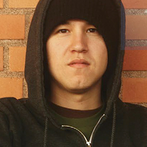 Young man from an Indigenous background in a hoodie standing by a wall