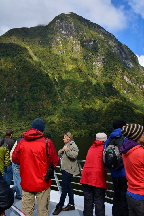 A tourist admires the view from a boat in Doubtful Sound
