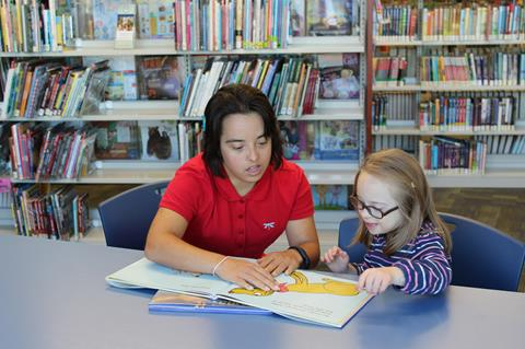 Photo of young woman with Down syndrome tutoring a child with Down syndrome.