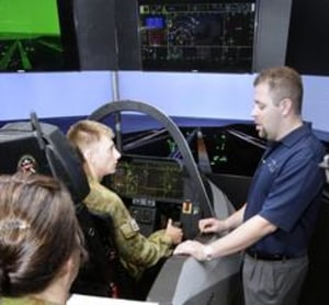 A Lockheed Martin Cockpit Demonstrator Engineer talks officer cadets through the F-35 Joint Strike Fighter simulator cockpit at RAAF Base Amberley. Credit: Defence