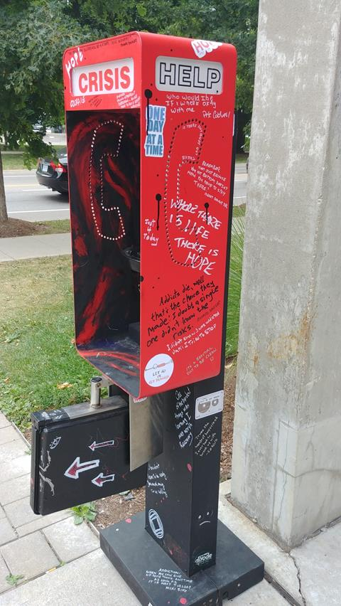 This is a photograph of the main library's new art installation, Crisis Phone 2020. It is an interactive art piece that utilizes recovered and restored urban artifacts in public spaces.