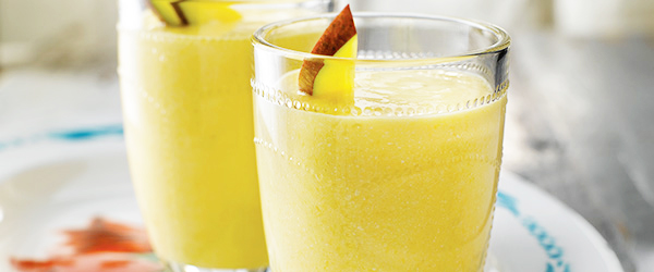 Photo of two glasses of mango smoothies on a springtime plate.