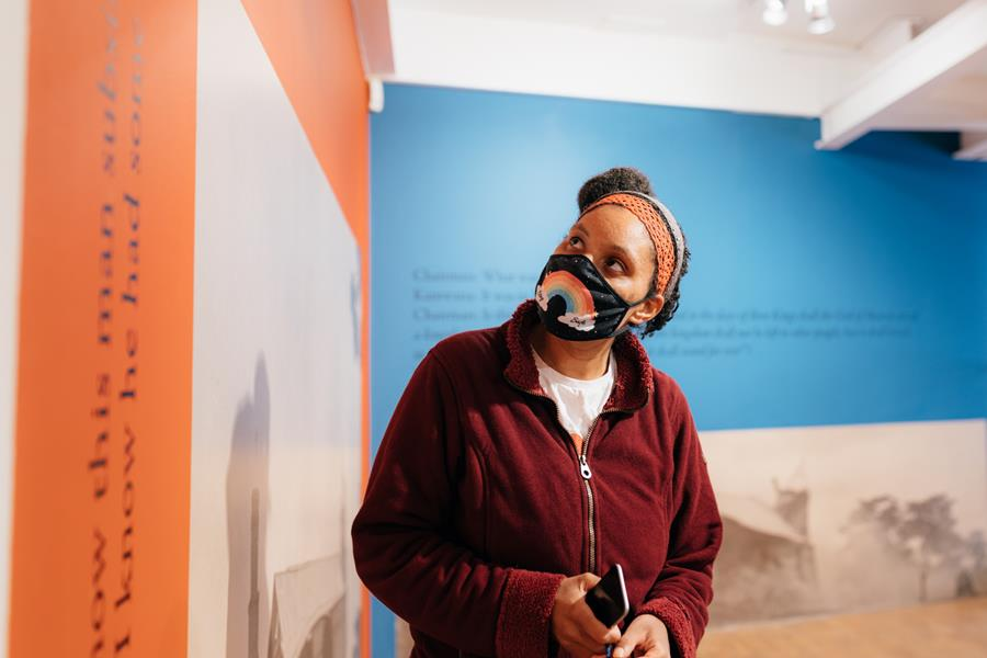 Image description: A person wearing a rainbow face mask looks at art work on a wall. The person wears a red fleece and has black hair, the art covering the wall features sepia photographs and a bright blue and orange background with blurred text.