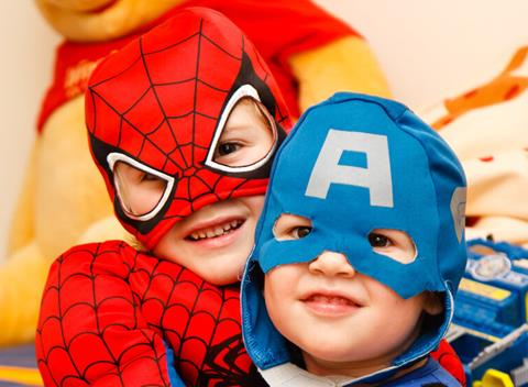 Two preschool aged boys. One has a spiderman costume on with mask on his face. The other boy looks smaller and as if sitting on the bigger boys lap has a face mask on that is blue and has an A on his forehead. The background is blurred with a large winnie the poo plush bear.