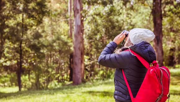 Person looking into nature with binoculars and a backpack.
