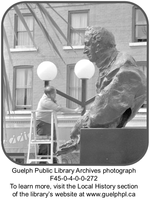 This is a photograph of a city of Guelph worker painting a new coat on the statue of John Galt - which is in front of the old city hall. The worker is standing on a ladder and hand-painting the statue. In the background, you can see the old white globe lamp posts and a brick apartment building.