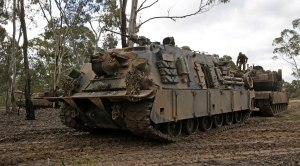 An Australian Army M88 Hercules recovery vehicle (L) prepares to tow a 'damaged' M1A1 Abrams tank during Exercise Reapers Run at Puckapunyal training area in July 2016.