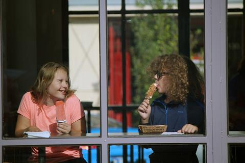 Photo of a girl with Down syndrome eating ice-cream with a friend.