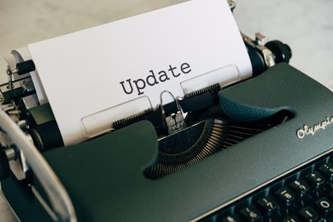 Black typewriter with white sheet of paper with the word Update centered on the page.