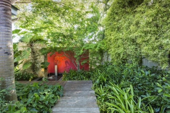 Tropical garden walkway with red wall
