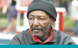 An elderly black man sitting in a park