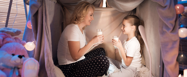 Mother and daughter eating cookies with milk in cozy blanket house at night at home.