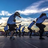 A youth group dances onstage at a festival.