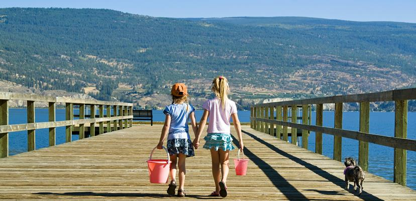 Two girls walk down a pier in Summerland BC
