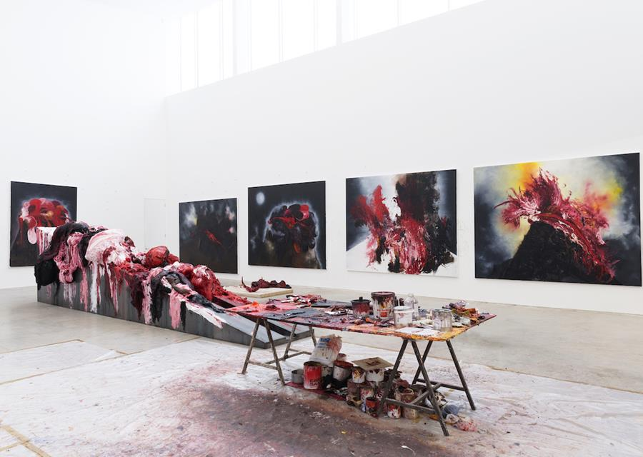 Image description: Five large abstract paintings in red, pink, black, yellow and grey, hanging on white walls in a large high-ceilinged room. At the centre of the room is a table covered in open paint pots, paint tubes and palettes. Behind the table, in front of the paintings, is a large abstract sculptural piece, consisting of a solid geometric base covered in bulbous shapes made of thick red, pink, white and black paint.