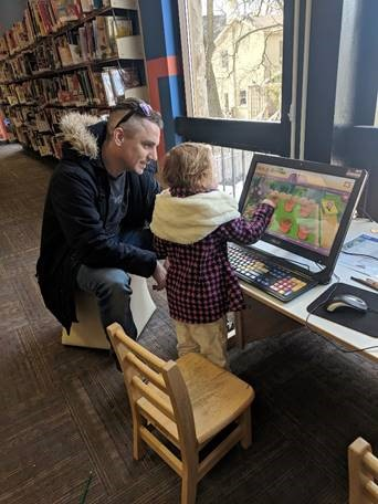 This is photograph of a father with his daughter sitting at the early literacy computer at the Main Library. She is pointing to the screen while playing a game.