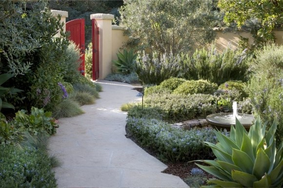 Mediterranean garden with pathway to red garden gate