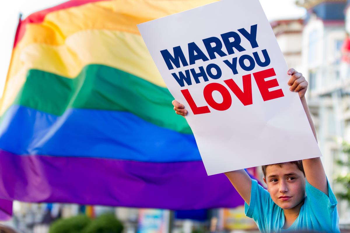 "Boy holding ""Marry Who You Love"" sign"