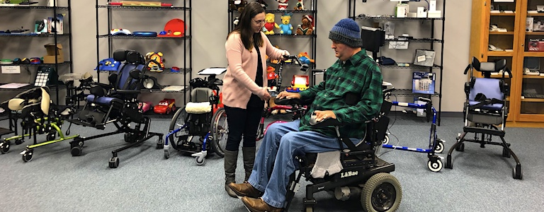 Jason Jones in a wheelchair and a facility coordinator at HDI CATS.