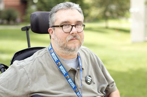 Man with salt and pepper hair and beard in wheelchair