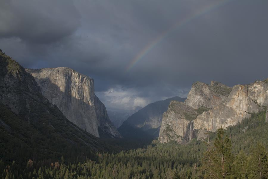 A wide-angle, dramatic shot of sun-soaked Tunnel View, with a faded rainbow visible over dramatic granite features and the expansive Valley below them.