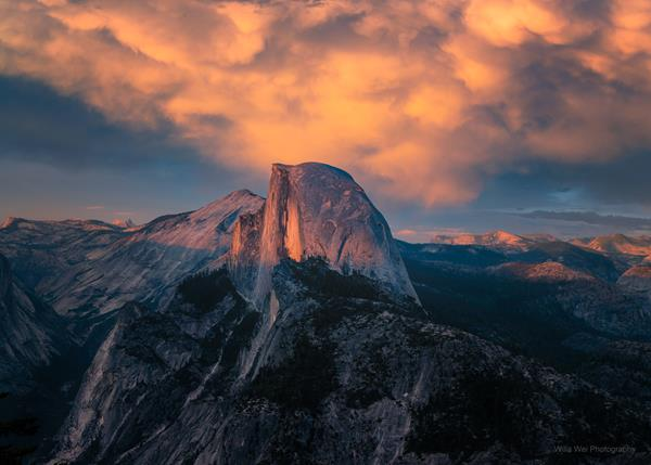 A remarkable sunset over Yosemite seen from Glacier Point, featuring peaches, pinks and blues and endless granite mountains behind famous Half Dome.
