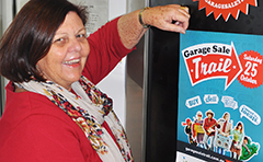 A photo of Mayor Gail Sellers hanging a poster to promote the Garage Sale Trail