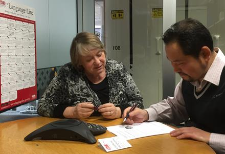 Image of 2 people sitting at a table with a telephone, depicting using an interpreter