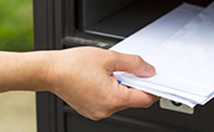 Hand retrieving mail from letterbox