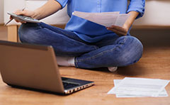person sitting on floor with laptop and paperwork
