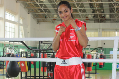 Image of Siona Fernandez standing in a boxing ring ready to box.