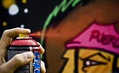 Photo of man graffiting wall