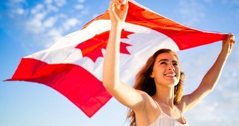 Young woman holding Canada flag in air