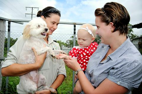 Dog pictured with a Local Laws officer and family