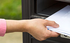 Lady taking mail from letter box.