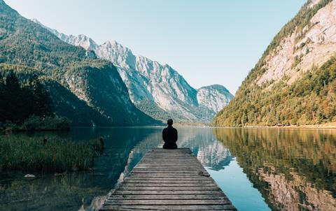 Person sitting on dock next to mountain lake